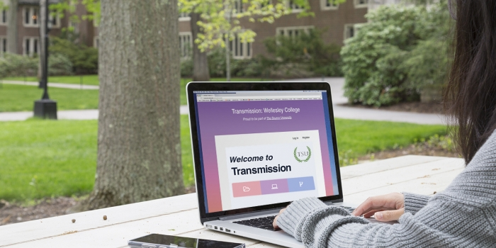 """A student sits at a picnic table in the academic quad looking at the screen of a laptop that reads, """"Welcome to Transmission"""""""