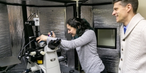 A student works with a microscope as a professor looks on