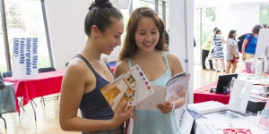 Sophia Ginsburg '20 and Katherine Kuang '20 peruse the Arts and Culture at Wellesley Calendar during student orientation.