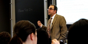 Professor Takis Metakas delivers a lecture at the front of a classroom.