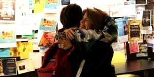 A student hugs her mother in the campus center