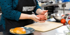 """A woman creates a ball of """"impossible burger."""""""