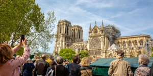 Tourists take photos of the Notre Dame cathedral after the April 2019 fire.