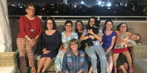 A group of Wellesley alumnae pose for a photo on a rooftop.