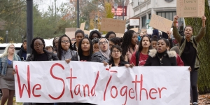 Students march with a We Stand Together banner