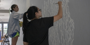 Two students work on a walled mural.