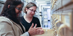 Two women look at a card catalogue in the archives.
