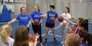 A group of student athletes lead a clinic with young girls.