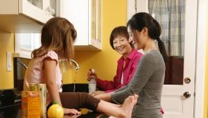 Three generations gathered around sink