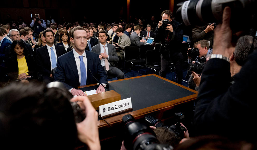 Mark Zuckerberg sitting at a table in Congress with media surrounding him