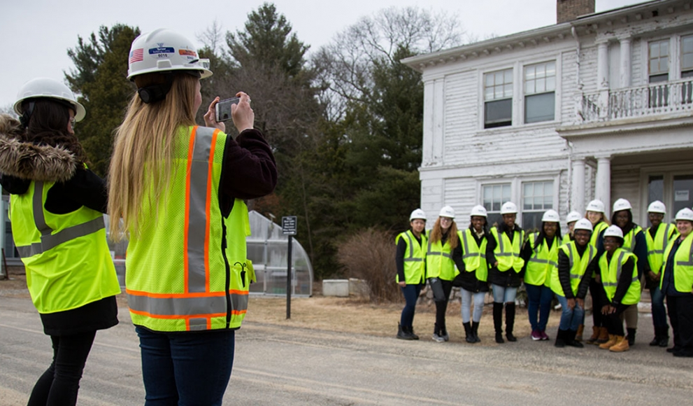 A group of students stand outside a building wearing construction vests and hard hats.