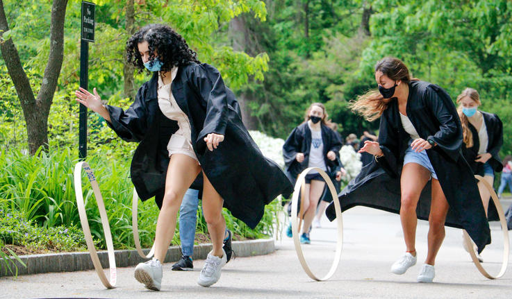 students hoop rolling wearing their robes