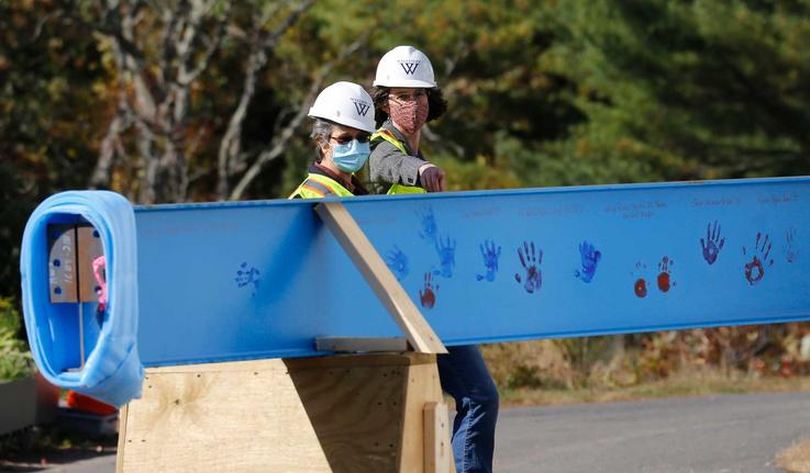 two people in construction gear looking at a construction beam