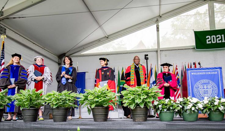 faculty standing on the commencment stage