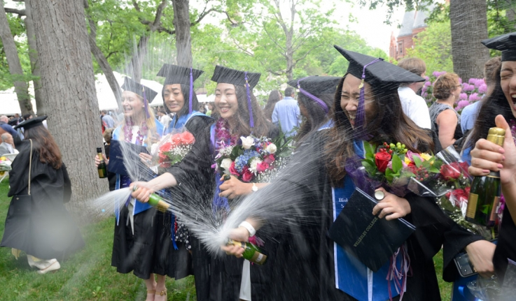 Members of the class of 2018 celebrate their graduation with Champagne.