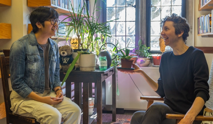 A professor talks to a student in front of a large assortment of plants in an office.