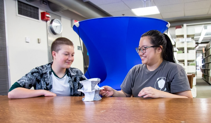 two students, Jenna Ocheltree '22 and Silvia Yu '21, sitting at a table in front of their math model
