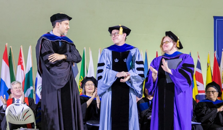 Three professors stand on stage at Wellesleys commencement exercises.