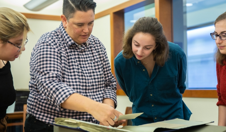 Wellesley College archivists talk with students in the archives. They look at a book.