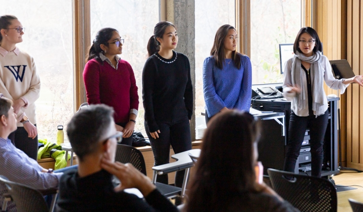 """Five students present a project in front of a crowd. One wears a Wellesley """"W"""" sweater."""