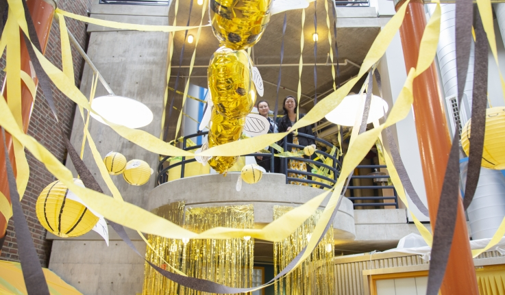 Two students look down on a section of the science center that was decorated in yellow streamers.
