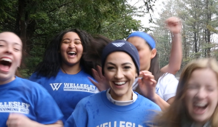 A Wellesley student runs with four teammates. They are dressed in Wellesley gear and cheer for her.