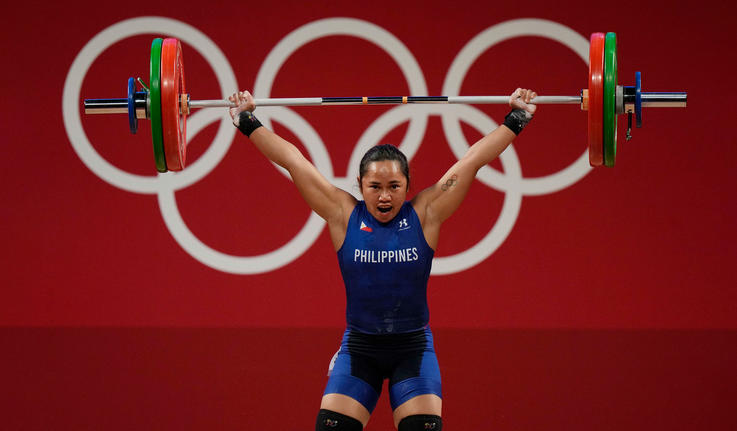 Hidilyn Diaz lifting weights above her head and looking strong