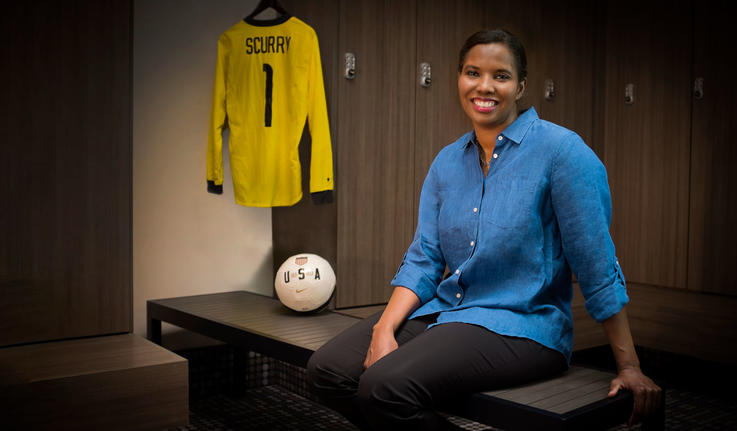 Briana Scurry posing on a bench with a soccer ball and jersey next to her