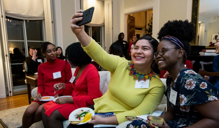 Students sit in the president's house, taking a selfie