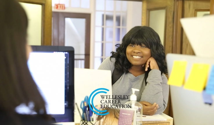 A student stands at a desk looking for help from someone in the Wellesley Career Education office.