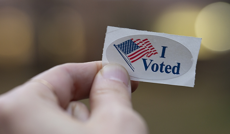 """A tight shot of a hand holding an """"I voted"""" sticker"""