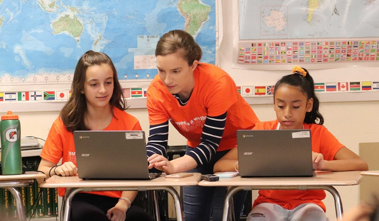 A professor works with two middle school female students at computers.