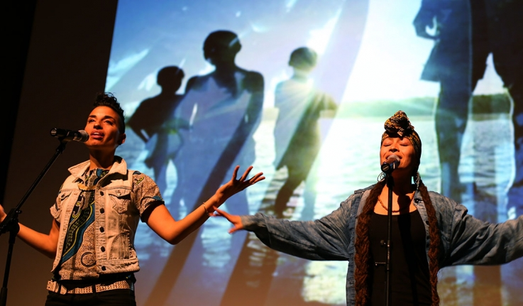 Two performers stand on stage in front of a multimedia presentation.