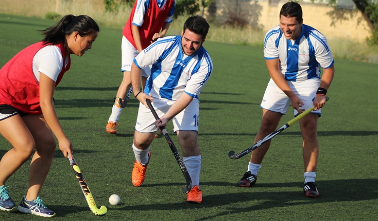 Wellesley Blue field hockey player teaches two people how to play field hockey in Greece.