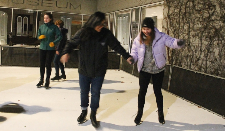 Two students ice skate on Davis Plaza
