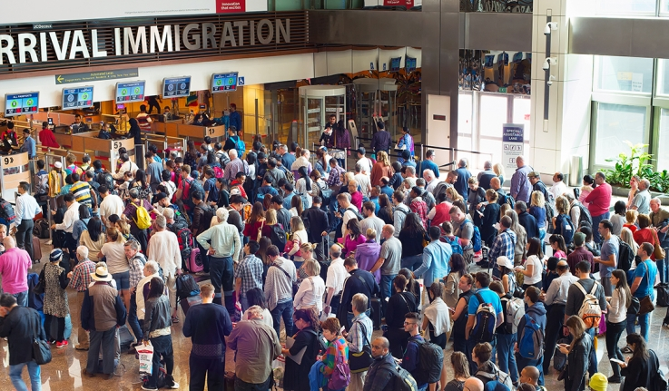 Hundreds of people stand in line at a transportation hub waiting to cross a boarder.