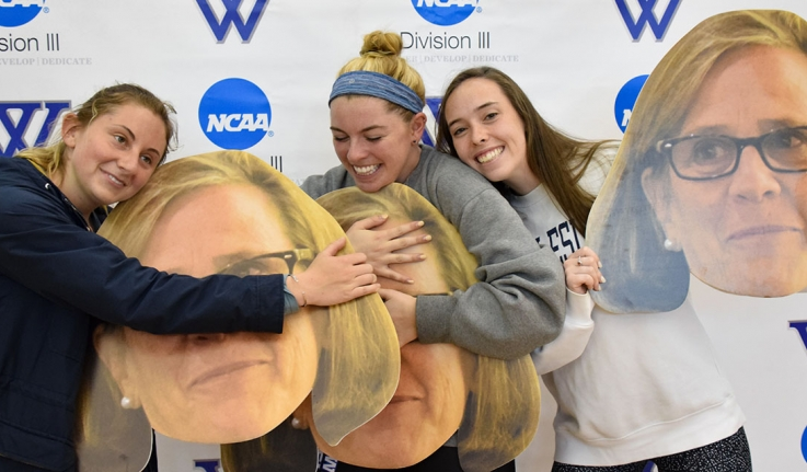 Student athletes pose hugging large cutouts of athletic director