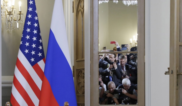 The American and Russian flags stand outside a conference room where members of the international press take photos.
