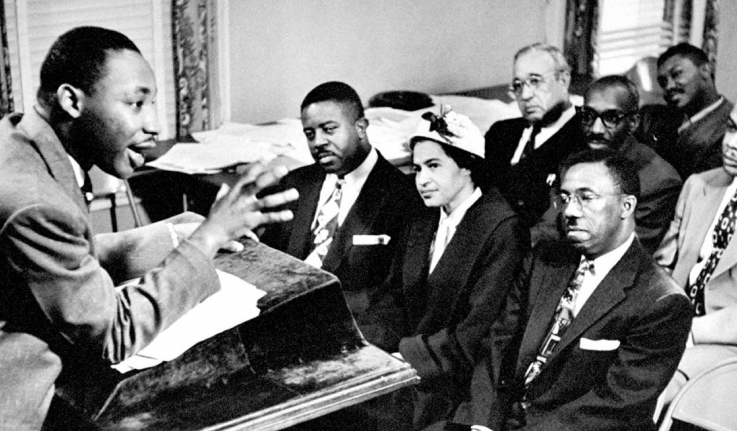Martin Luther King talks to activists from a podium in a small room