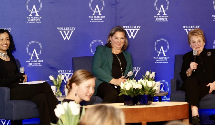 Three women talk on a stage