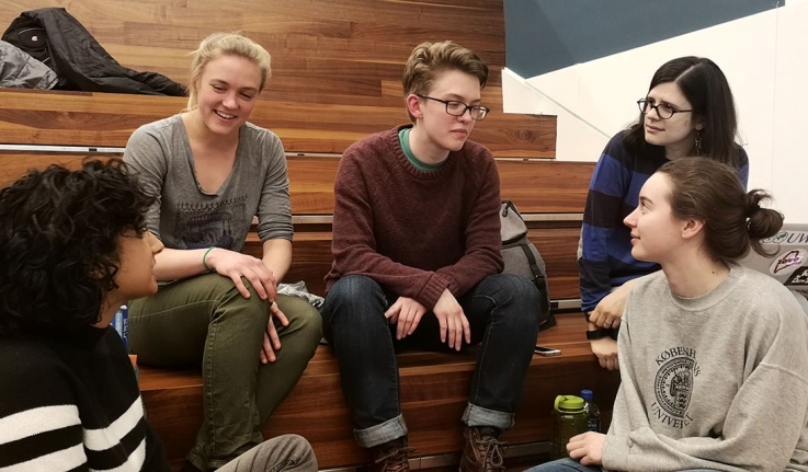 Five Wellesley students sit on bleachers discussing strategy at BOW Datafest