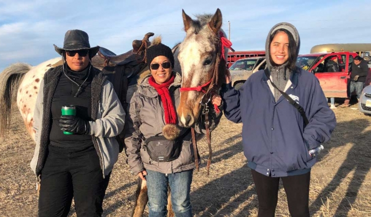 A professor and two alumnae stand with a horse