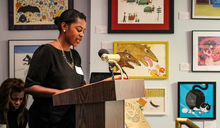 A woman speaks from a podium with artwork all around her