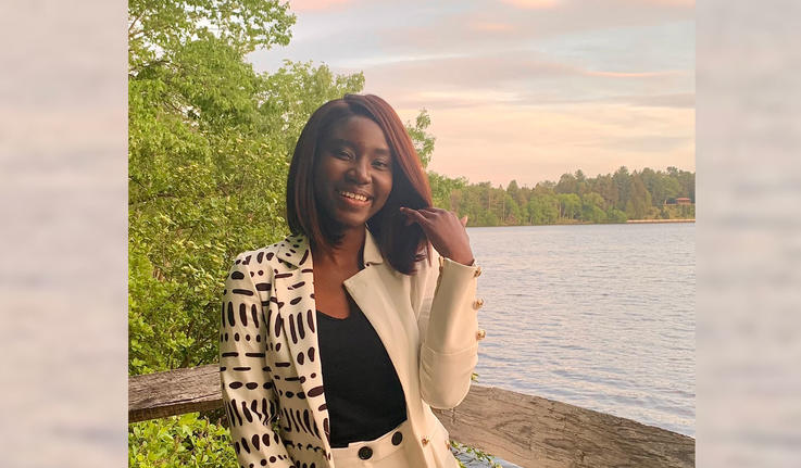 Adwoa Difie Antwi '21 posing in front of Lake Waban with a sunset sky