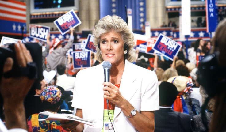 A woman reporter stands on the floor of a press room.