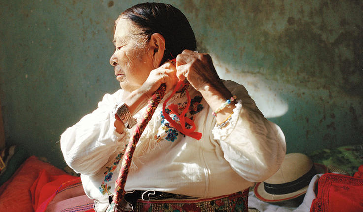 A photo of an older Hispanic woman braiding her long hair.