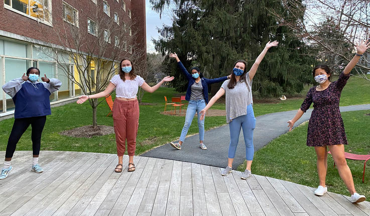 people wearing masks and posing with their hands up in the air
