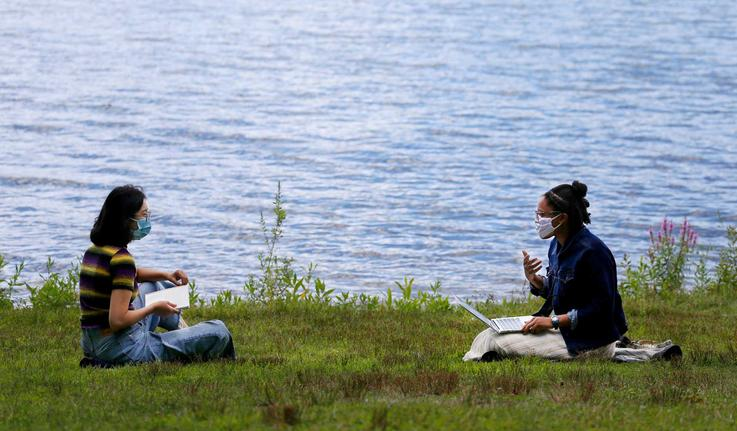 two students sitting by the lake reading books and talking