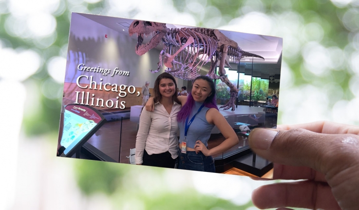 Two students in a postcard standing in front of a skeleton dinosaur.