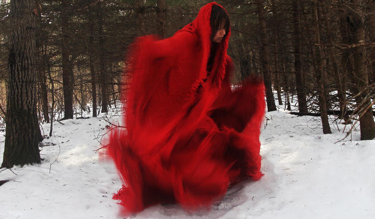 A photo shows a woman in movement, wearing a red blanket-like dress and surrounded by trees with snow on the ground.